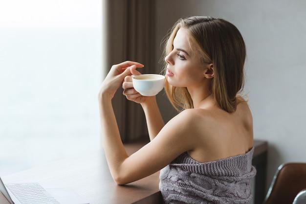 Jolie jeune femme sensuelle en couverture grise assise à la table et buvant du café