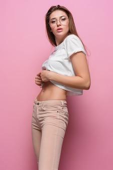 Jolie jeune femme sensuelle de mode sexy posant sur rose vêtue de jeans de style hipster