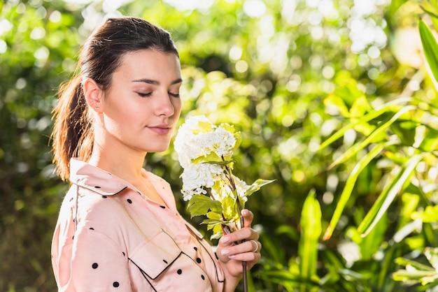 Jolie jeune femme sentant les fleurs blanches