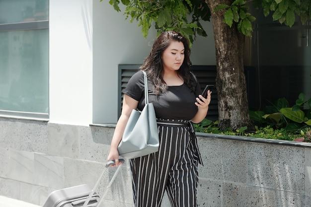 Jolie jeune femme sérieuse avec des bagages marchant dans la rue et vérifiant les messages texte sur smartohone