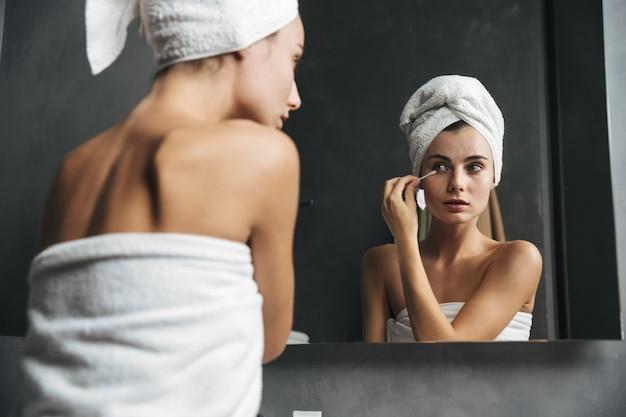 Jolie jeune femme avec une serviette sur la tête se démaquiller avec un coton-tige en face du miroir dans la salle de bains