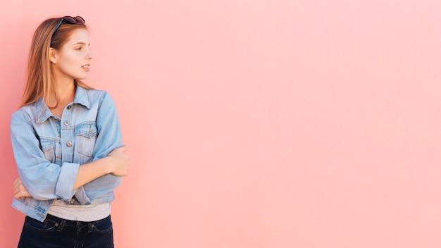 Jolie jeune femme avec ses bras croisés à la recherche de suite sur fond rose