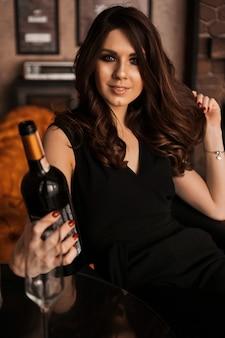 Jolie jeune femme sexy aux cheveux longs tenant une bouteille de vin