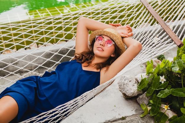 Jolie jeune femme sexy en robe bleue et chapeau de paille portant des lunettes de soleil roses se détendre en vacances allongé dans un hamac