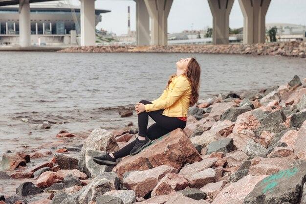 Jolie jeune femme sexy de silhouette athlétique dans des vêtements lumineux marchant sur le littoral en ville. promenade dans la plage de la mer de la ville. portrait de jolie femme mignonne en veste jaune et pantalon noir sur la côte de la mer