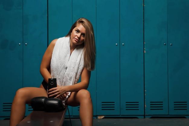 Jolie jeune femme avec une silhouette athlétique avec une bouteille d'eau dans un club de sport de vestiaire, avec une serviette et des gants de boxe
