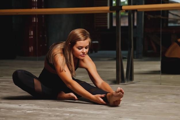 Jolie jeune femme slave en uniforme de sport s'entraîne en soirée dans une ancienne salle de sport, faisant des exercices d'étirement devant un miroir. concept de mode de vie sain, de sport et d'exercice en salle de sport. espace de copie