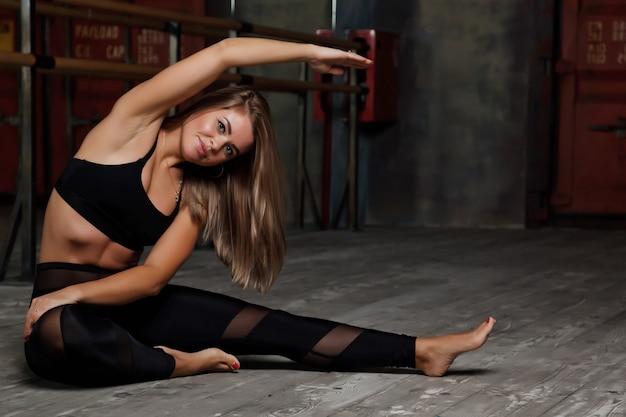 Jolie jeune femme slave en uniforme de sport s'entraîne en soirée dans une ancienne salle de sport