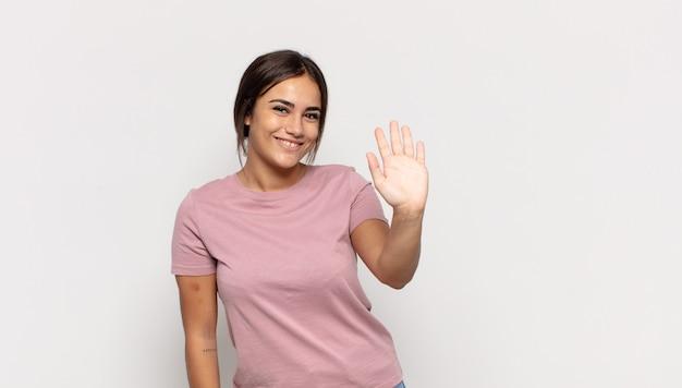Jolie jeune femme souriant joyeusement et gaiement, agitant la main, vous accueillant et vous saluant, ou vous disant au revoir