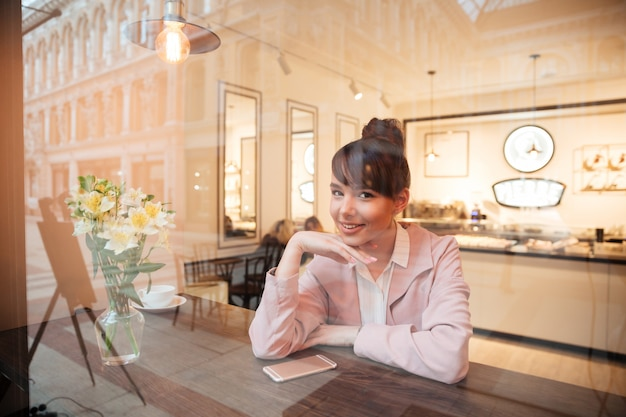 Jolie jeune femme souriante assise à la table du café à l'intérieur