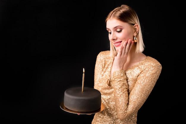 Jolie jeune femme souriante aux cheveux blonds souhaitant tout en regardant le gâteau d'anniversaire recouvert de pâte d'amande noire avec bougie allumée