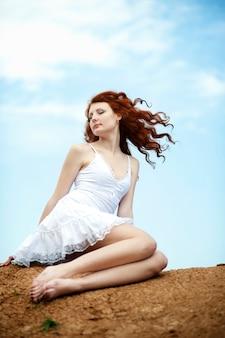 Jolie jeune femme souriante aux cheveux rouges flottant au vent