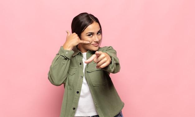 Jolie jeune femme souriante joyeusement et pointant tout en faisant un appel, vous geste plus tard, parler au téléphone