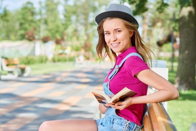 Jolie jeune femme souriante joyeusement relaxante dans le parc local appréciant la lecture d'un livre copyspace bonheur hipster mode de vie loisirs détente étudiant éducation étude apprentissage concept