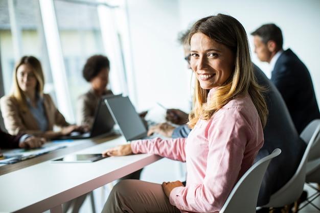 Jolie jeune femme souriante lors d'une réunion d'affaires réussie dans le bureau moderne