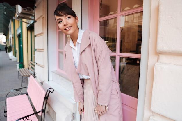 Jolie jeune femme souriante en manteau rose debout à l'extérieur du café