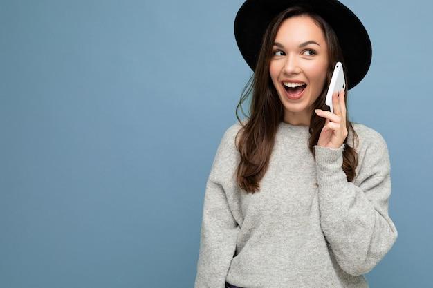 Jolie jeune femme souriante parlant portant un chapeau noir et un pull gris tenant un smartphone