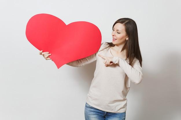 Jolie jeune femme souriante pointant grand coeur rouge dans les mains isolés sur fond blanc. copiez l'espace pour la publicité. avec place pour le texte. concept de la saint-valentin ou de la journée internationale de la femme.