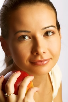 Jolie jeune femme souriante avec pomme rouge.