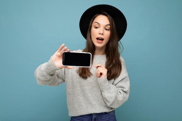 Jolie jeune femme souriante portant un chapeau noir et un pull gris tenant le smartphone regardant vers le bas