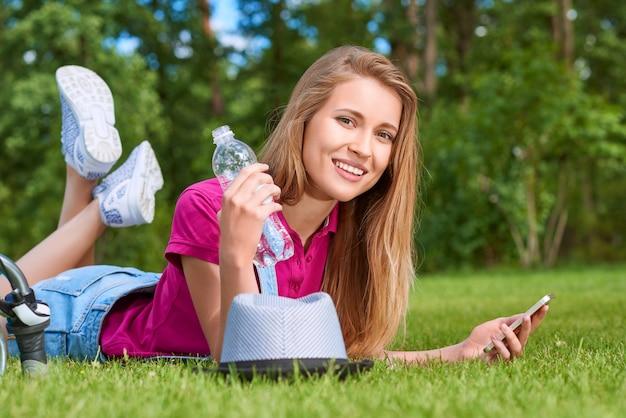 Jolie jeune femme souriante en position couchée sur l'herbe dans le parc à l'aide de son téléphone intelligent internet wifi connectivité mode de vie détente week-end de loisirs.