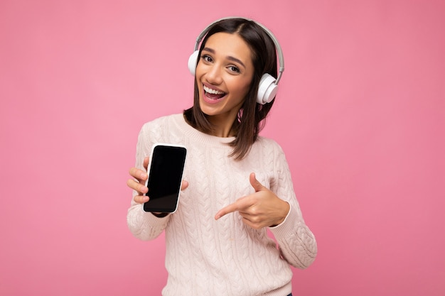 Jolie jeune femme souriante et positive portant une tenue décontractée élégante isolée sur un mur de fond coloré tenant et montrant un téléphone portable avec un écran vide pour la découpe portant un casque bluetooth blanc