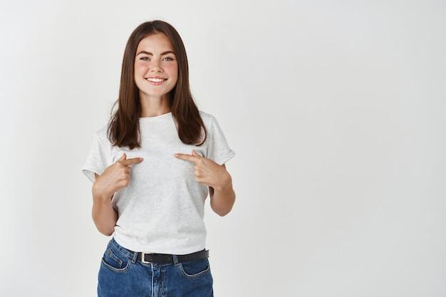 Jolie jeune femme souriante et se montrant du doigt, vous avez besoin de moi geste, debout sur un mur blanc