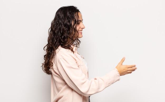 Jolie jeune femme souriante, vous saluant et vous offrant une poignée de main pour conclure une affaire réussie