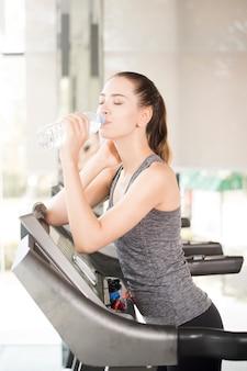 Jolie jeune femme sportive boit de l'eau sur un tapis roulant dans une salle de sport, mode de vie sain