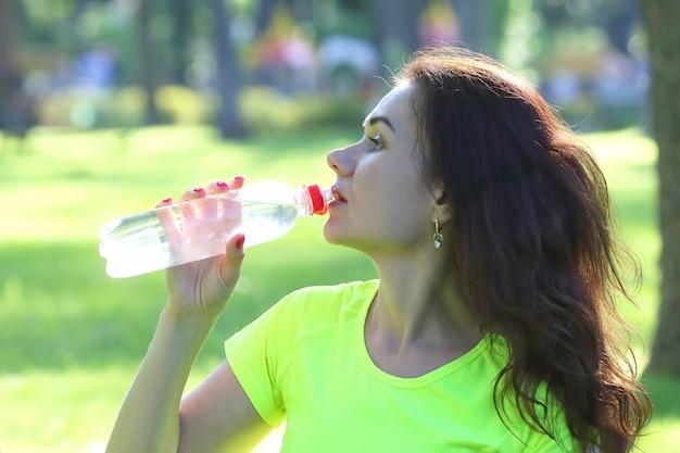 Jolie jeune femme sportive de l'eau potable à partir d'une bouteille