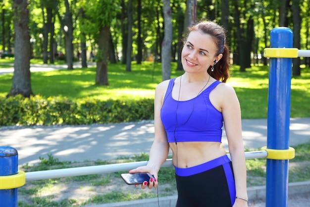 Jolie jeune femme sportive écoutant de la musique lors d'une promenade