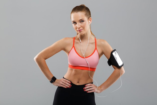 Jolie jeune femme sportive, écouter de la musique par téléphone mobile