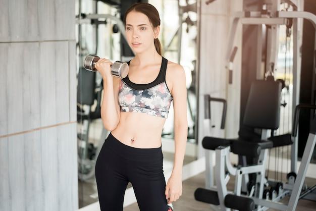 Jolie jeune femme sportive est workout in gym, mode de vie sain