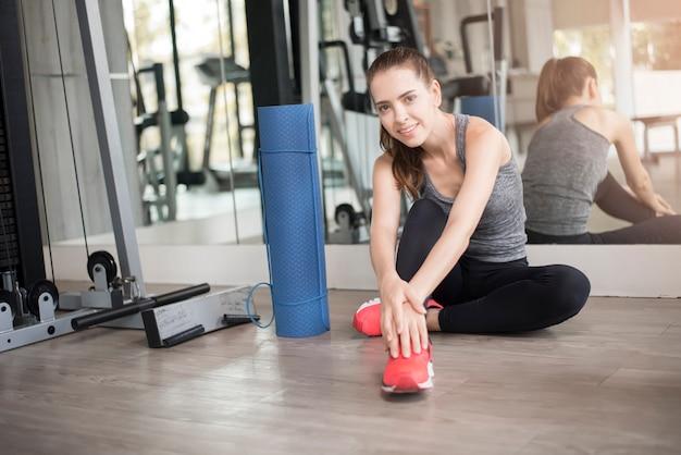 Jolie jeune femme sportive se réchauffe dans une salle de sport, mode de vie sain