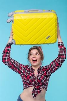 Jolie jeune femme surprise dans une chemise à carreaux tient une valise jaune sur sa tête posant contre un