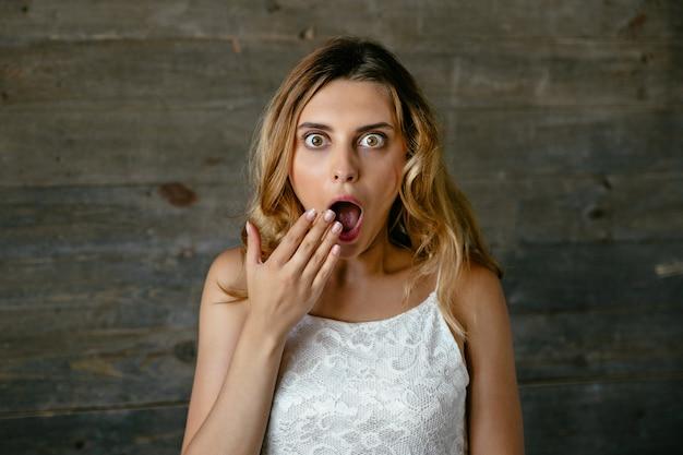 Jolie jeune femme surprise de quelque chose, couvrant sa bouche ouverte à la main