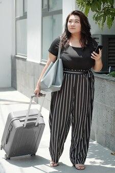 Jolie jeune femme en t-shirt noir et pantalon rayé marchant avec une valise