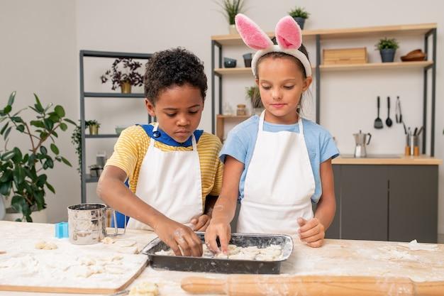 Jolie jeune femme en tablier debout près de son petit fils rouler la pâte maison pour la pâtisserie sur la table