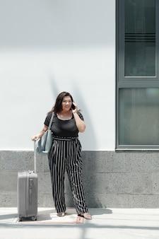 Jolie jeune femme de taille plus debout à l'extérieur avec une valise et un sac et parlant au téléphone avec un chauffeur de taxi