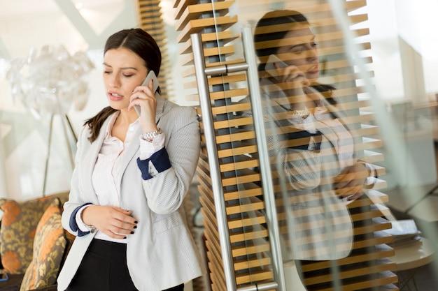 Jolie jeune femme avec téléphone portable dans le bureau moderne