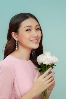 Jolie jeune femme tenant un bouquet de roses blanches isolées sur fond vert pastel