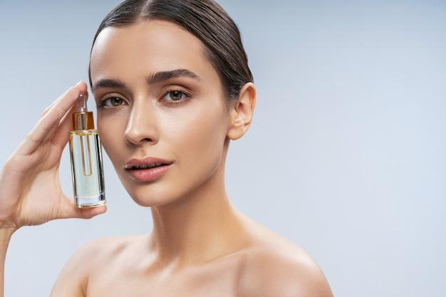 Jolie jeune femme tenant une bouteille de sérum facial
