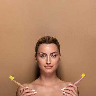 Jolie jeune femme tenant des brosses à dents