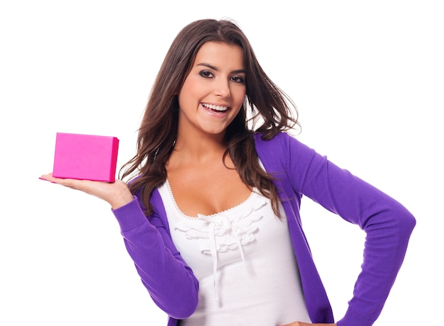 Jolie jeune femme tenant un cadeau rose