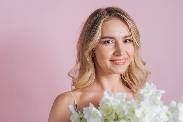 Une jolie jeune femme tenant une fleur blanche fraîche