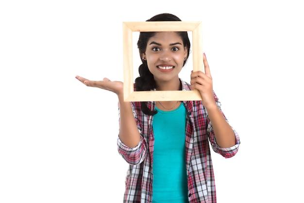 Jolie jeune femme tenant et posant avec cadre photo sur fond blanc.