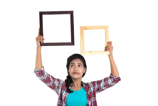 Jolie jeune femme tenant et posant avec cadre photo sur un mur blanc.