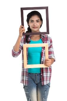 Jolie jeune femme tenant et posant avec cadre photo.
