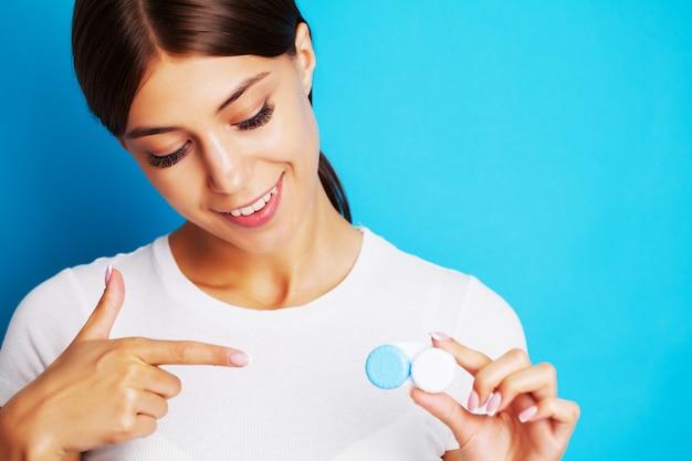 Jolie jeune femme tenant un récipient avec des lentilles de contact pour la vue