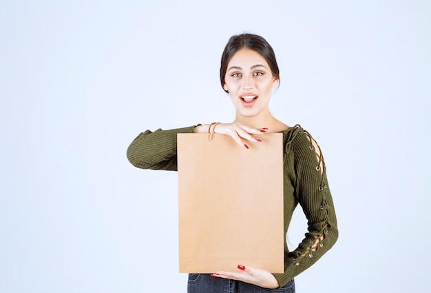 Jolie jeune femme tenant un sac en papier sur fond blanc.